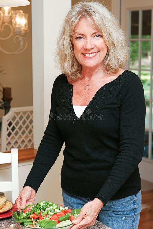 Mujer madura sana con la ensalada imagen de archivo libre de regalías