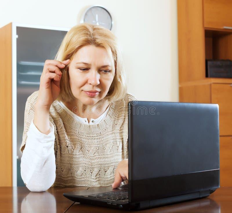 Mujer madura seria con el ordenador portátil fotos de archivo