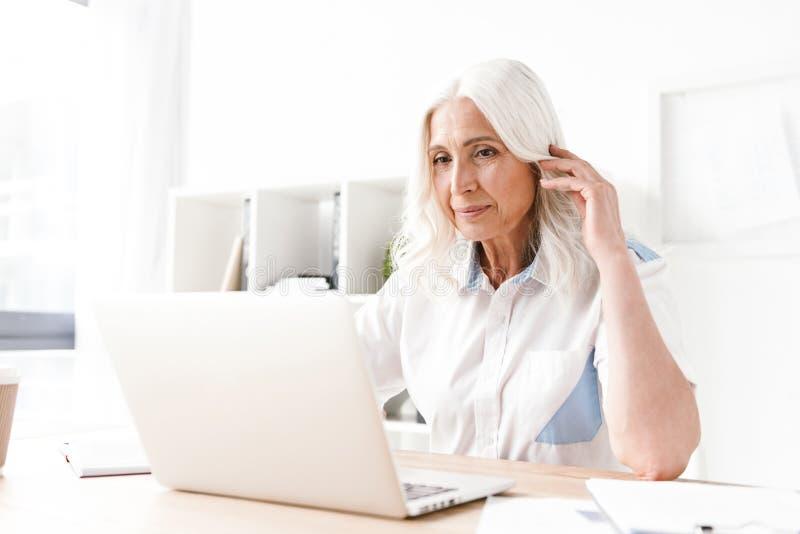 Mujer madura seria que se sienta dentro en el funcionamiento de la oficina fotografía de archivo libre de regalías