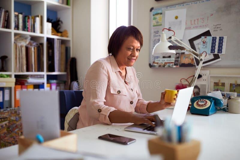 Mujer madura sonriente con el funcionamiento del ordenador portátil en Ministerio del Interior imagenes de archivo