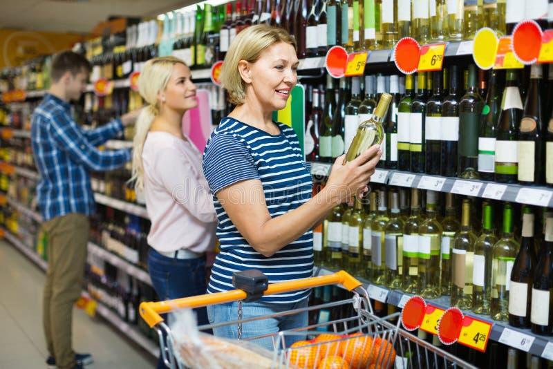 Mujer madura sonriente del positivo en la sección del vino imagen de archivo libre de regalías