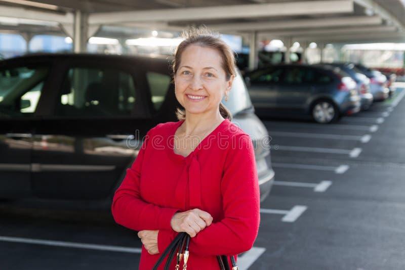 Mujer madura sonriente en el estacionamiento imagen de archivo