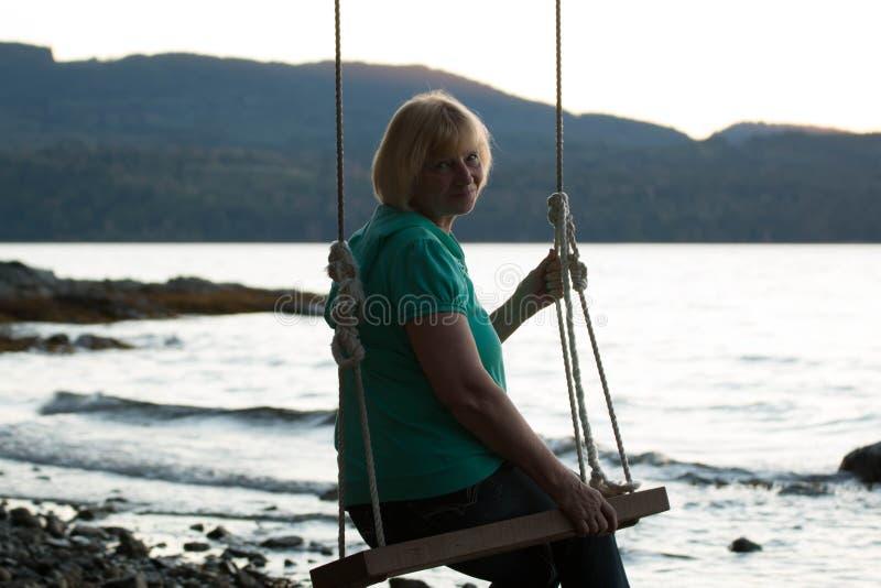 Mujer madura sonriente en el oscilación en la playa imagenes de archivo