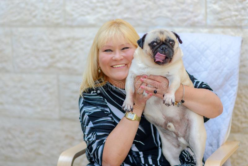 Mujer madura sonriente feliz con el perro casero al aire libre imagen de archivo