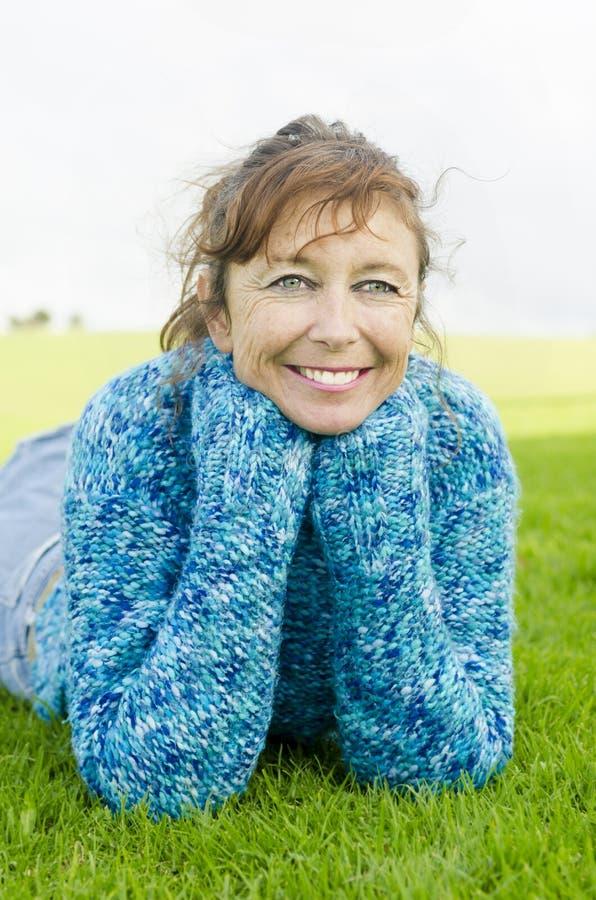 Mujer madura sonriente feliz que pone en hierba fotografía de archivo