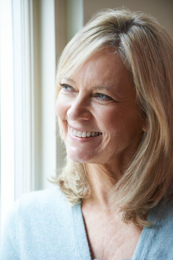 Mujer madura sonriente que mira fuera de ventana fotos de archivo