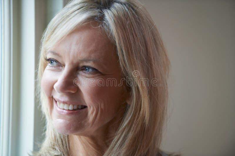 Mujer madura sonriente que se coloca al lado de ventana foto de archivo