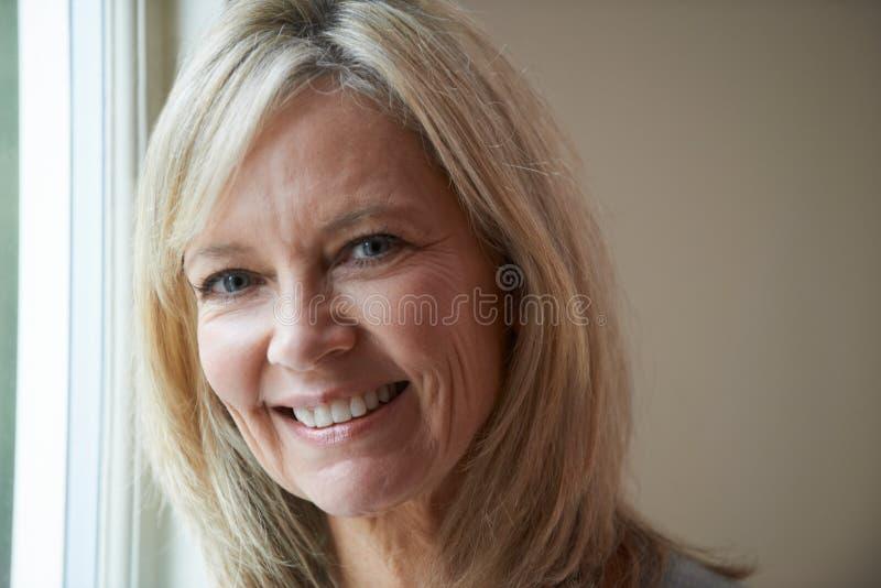 Mujer madura sonriente que se coloca al lado de ventana imagen de archivo libre de regalías
