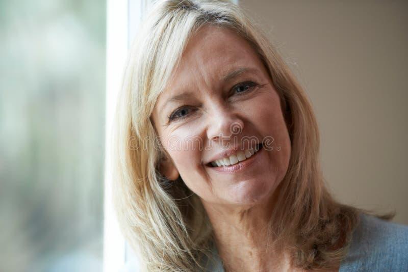Mujer madura sonriente que se coloca al lado de ventana imagen de archivo