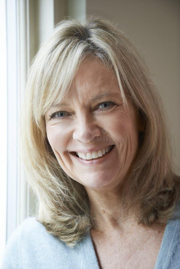 Mujer madura sonriente que se coloca al lado de ventana imagenes de archivo