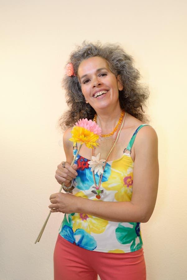 Mujer madura sonriente que sostiene el equipo del verano de las flores fotos de archivo