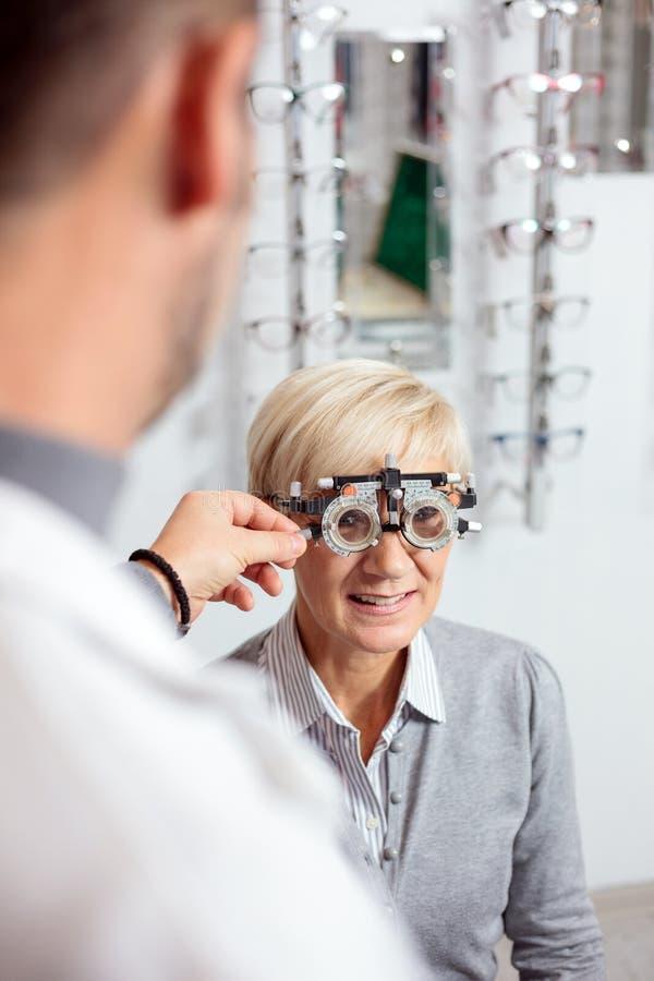 Mujer madura sonriente que tiene examen de la vista y medida de la dioptría de un optometrista de sexo masculino fotografía de archivo