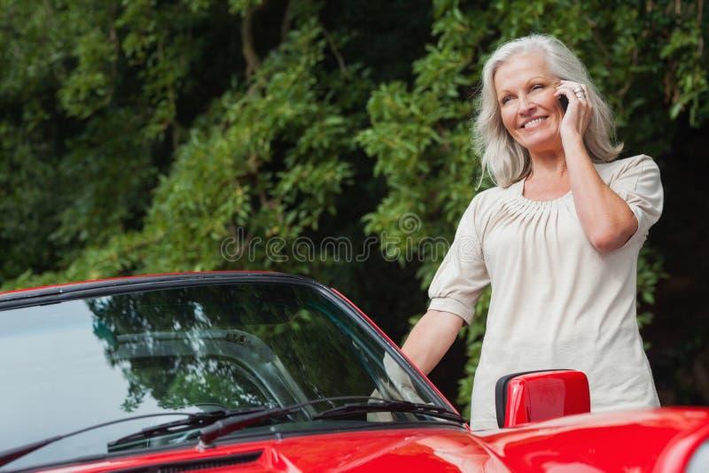 Mujer madura sonriente que tiene llamada de teléfono imagen de archivo libre de regalías