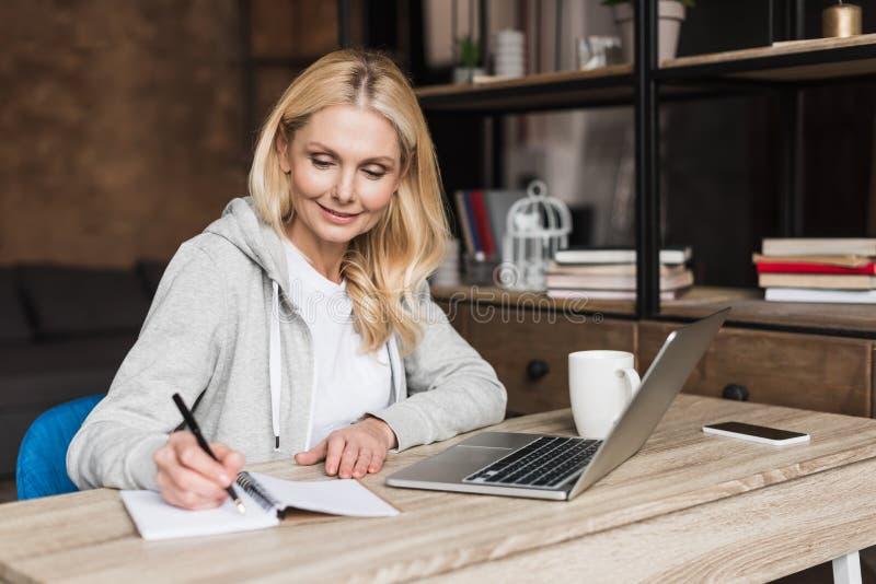mujer madura sonriente que toma notas y que usa el ordenador portátil en casa imagen de archivo libre de regalías