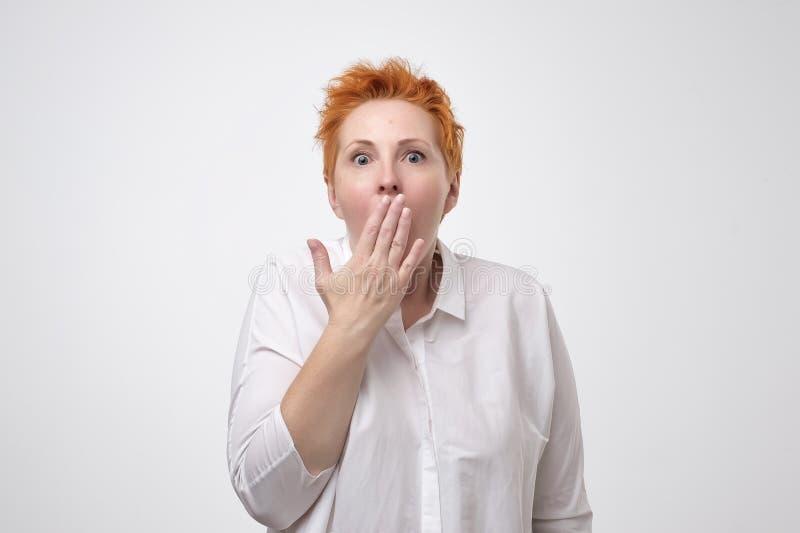 Mujer madura sorprendida con la boca roja de la cubierta del pelo corto con la mano y el mirar fijamente la cámara Concepto impac imagenes de archivo
