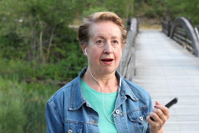 Mujer madura sorprendida que habla en el teléfono celular al aire libre foto de archivo libre de regalías