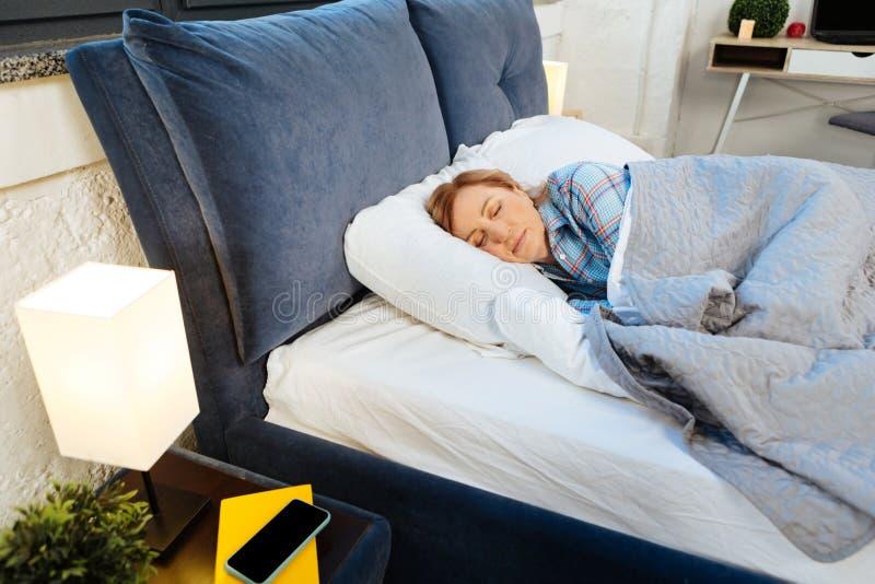 Mujer madura tranquila que miente en su cama cubierta y caliente foto de archivo