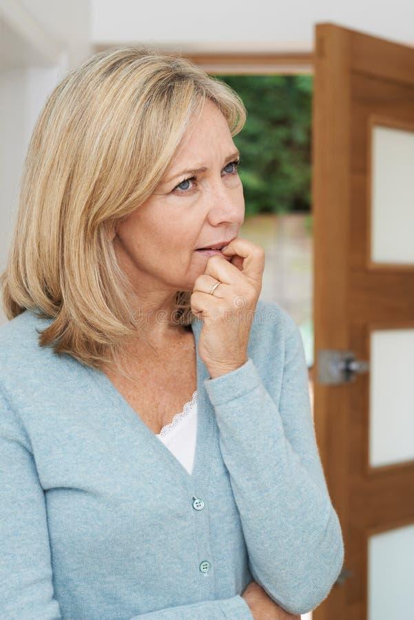 Mujer madura triste que sufre de la agorafobia que mira fuera de abierto imágenes de archivo libres de regalías
