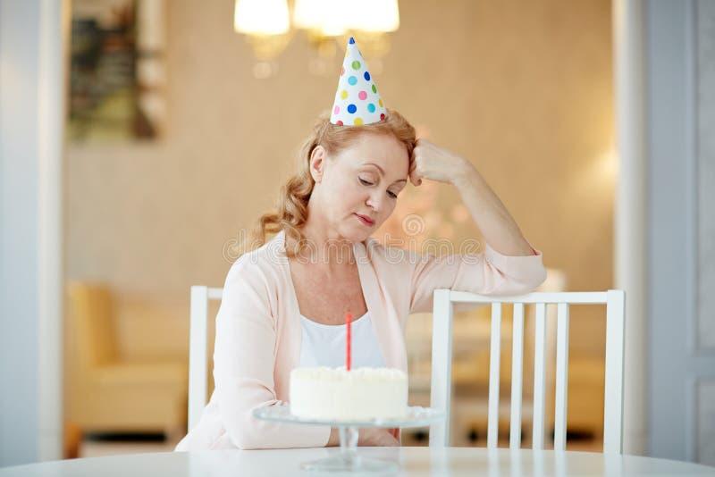 Mujer madura triste solamente con la torta de cumpleaños imagen de archivo