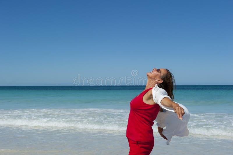 Mujer madura y confidente feliz en el océano fotos de archivo