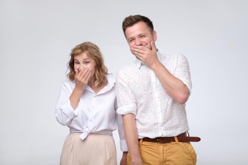 Mujer madura y hombre que ríen nerviosamente juntas cubriendo sus bocas con las manos que intentan ser tranquilo fotos de archivo