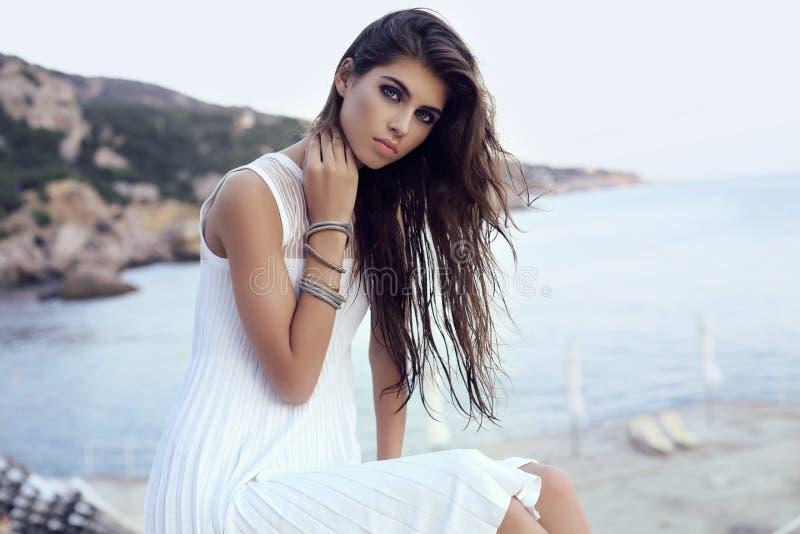 Mujer magnífica con el pelo oscuro en vestido elegante en la playa imagen de archivo
