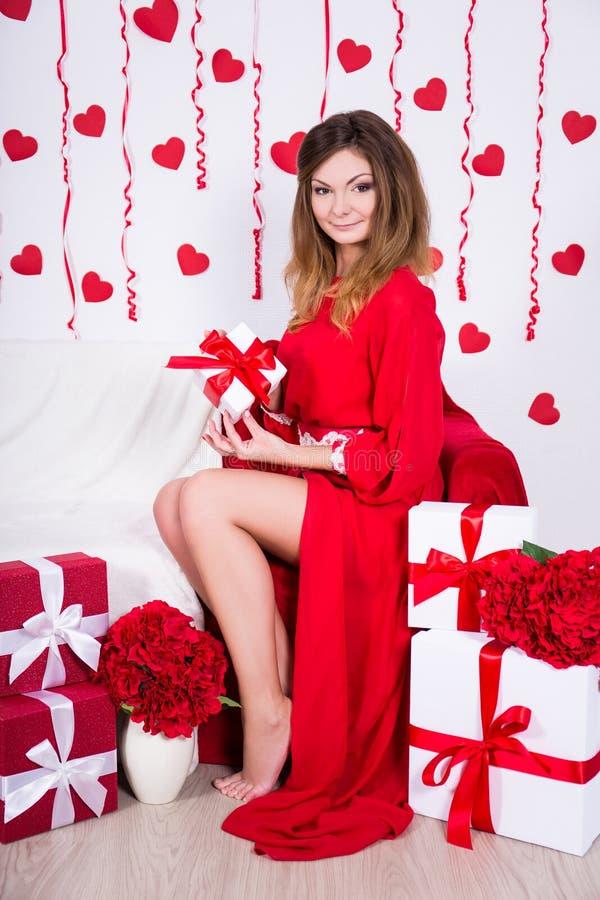 Mujer magnífica en el vestido rojo que se sienta en sitio adornado con el flowe imágenes de archivo libres de regalías