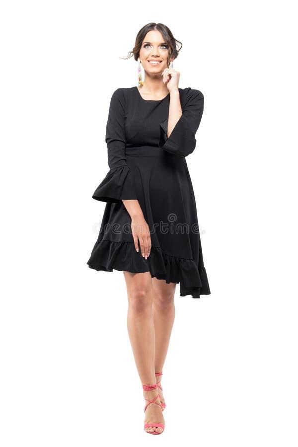 Mujer magnífica en vestido negro que camina y que mira para arriba con la mano en la barbilla fotos de archivo libres de regalías