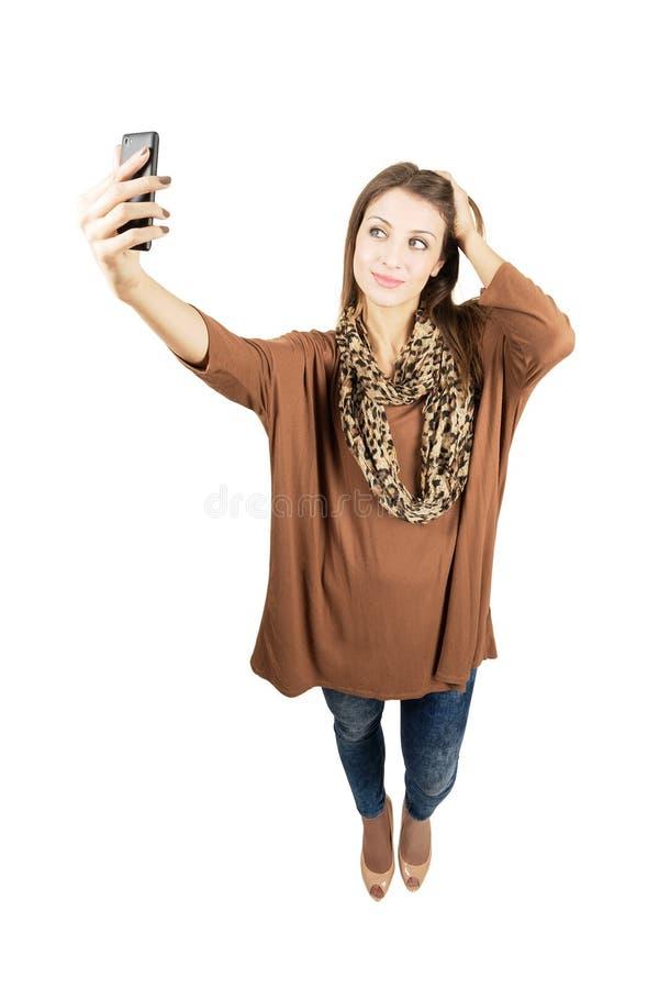 Mujer magnífica joven que toma el autorretrato o el selfie con smartphone fotografía de archivo libre de regalías