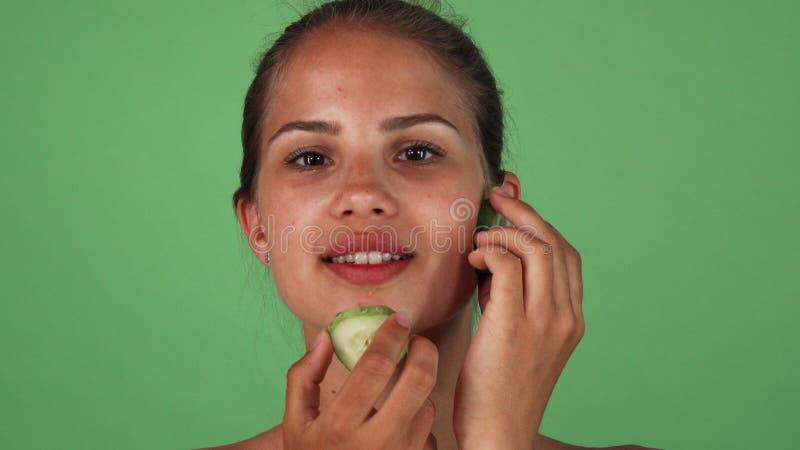 Mujer magnífica que da masajes a su cara con las rebanadas de pepino foto de archivo libre de regalías