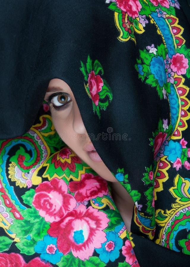 Mujer magnífica que hace la cara cubrir por la bufanda fotos de archivo libres de regalías