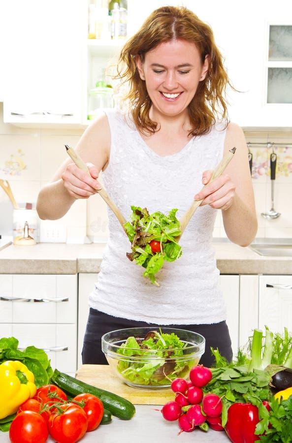 Mujer magnífica que mezcla una ensalada en su cocina imagen de archivo libre de regalías