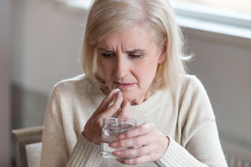 Mujer mal mayor insegura sobre tomar medicinas en casa fotos de archivo libres de regalías
