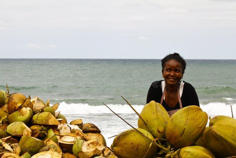 Mujer malgache que vende los cocos en la playa imagen de archivo