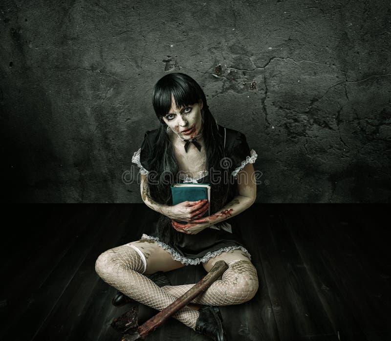 Mujer malvada que sostiene el libro y el hacha sangrienta imagen de archivo libre de regalías