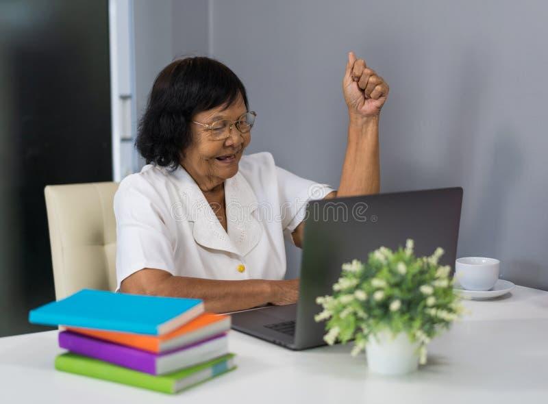 Mujer mayor acertada que trabaja en el ordenador portátil con los brazos aumentados imágenes de archivo libres de regalías