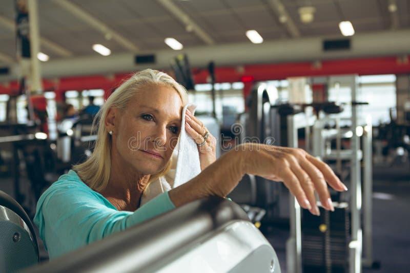 Mujer mayor activa cansada que limpia la toalla sudada en estudio de la aptitud imagen de archivo