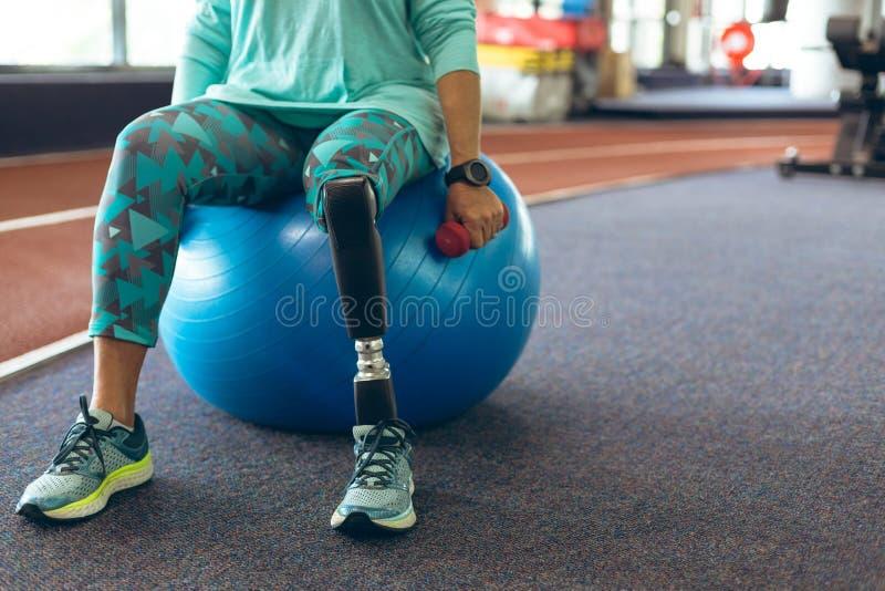 Mujer mayor activa discapacitada que ejercita con pesa de gimnasia mientras que se sienta en bola del ejercicio imagen de archivo