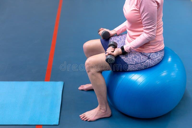 Mujer mayor activa que ejercita con pesa de gimnasia en centro de deportes foto de archivo