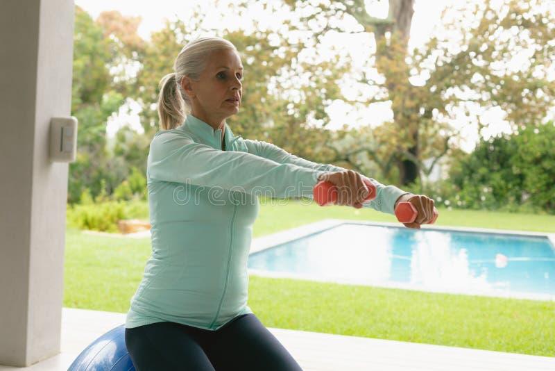 Mujer mayor activa que ejercita con pesa de gimnasia en pórtico en casa imágenes de archivo libres de regalías