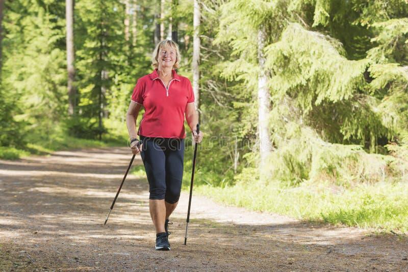 Mujer mayor activa que hace ejercicio nórdico del paseo foto de archivo libre de regalías