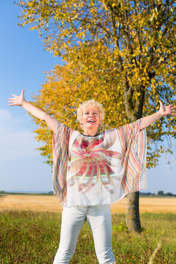 Mujer mayor activa que siente libre y feliz mientras que coloca outdoo imagen de archivo