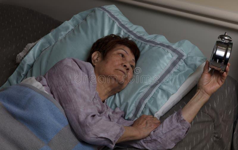 Mujer mayor agitada que se deslumbra en el despertador durante wh de la noche fotografía de archivo