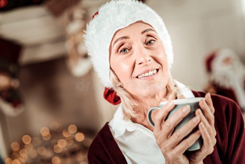 Mujer mayor agradable que celebra una taza y una sonrisa fotos de archivo