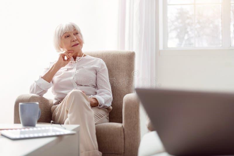 Mujer mayor agradable que escucha alguien que habla con ella fotografía de archivo
