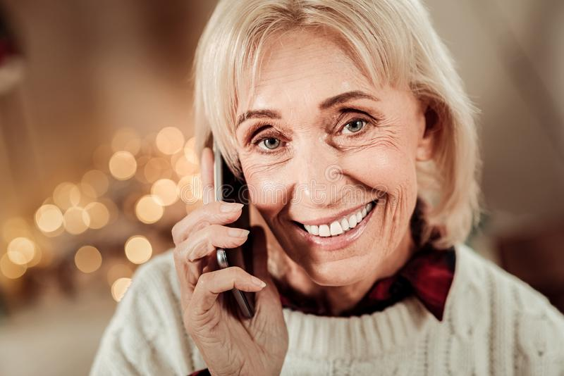 Mujer mayor agradable que sonríe y que tiene conversación fotografía de archivo