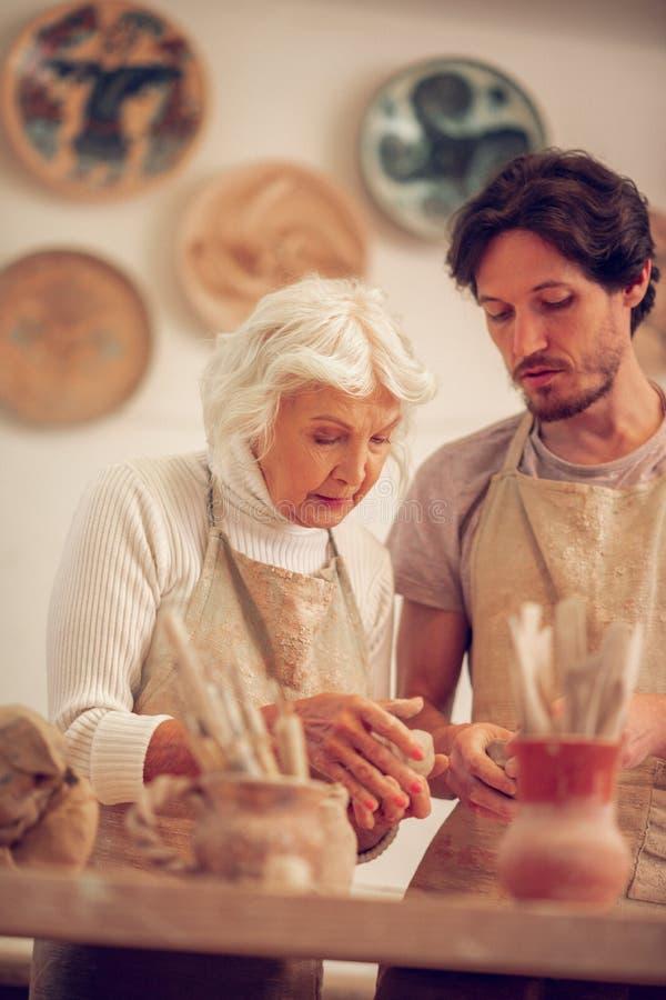 Mujer mayor agradable que trabaja con su aprendiz imagenes de archivo