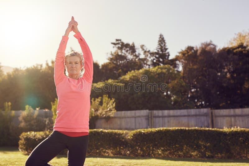 Mujer mayor al aire libre en la actitud de la yoga para la balanza y el foco imagen de archivo