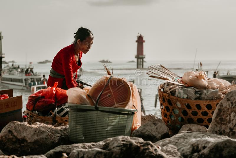 Mujer mayor al preparar mercancías antes a través del estrecho de Badung fotografía de archivo