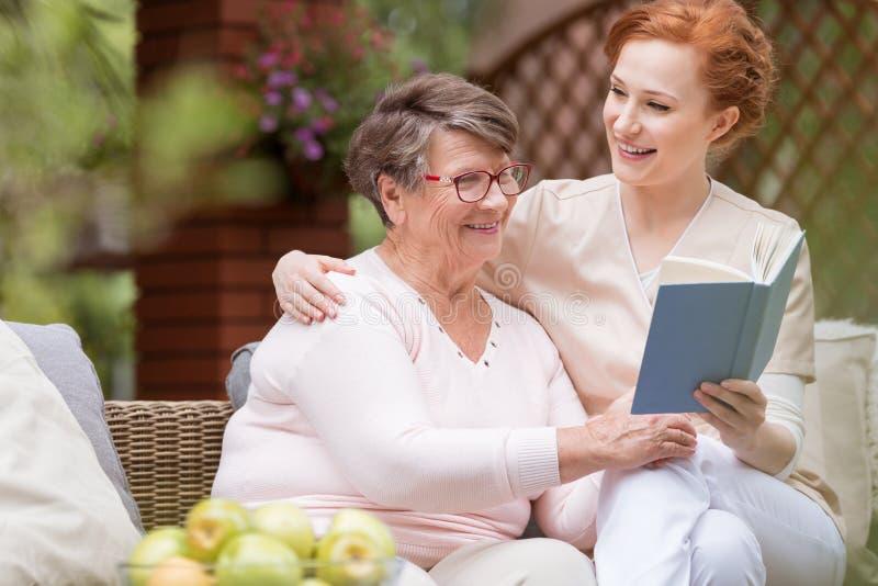 Mujer mayor alegre con su vigilante blando que lee un libro t imagenes de archivo